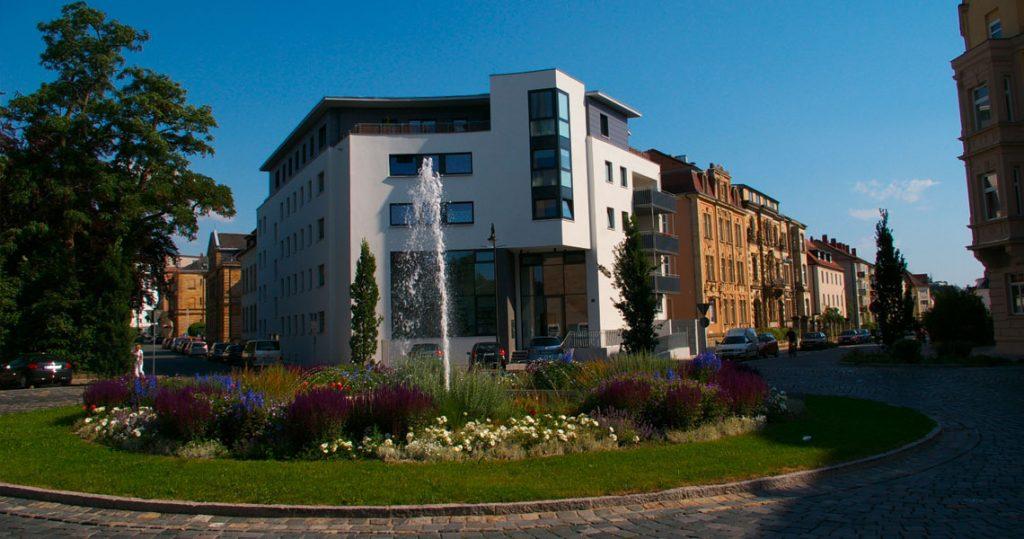 Wilhelmsplatz in Bayreuth mit Springbrunnen, dahinter das Gebaeude mit Architekturbuero