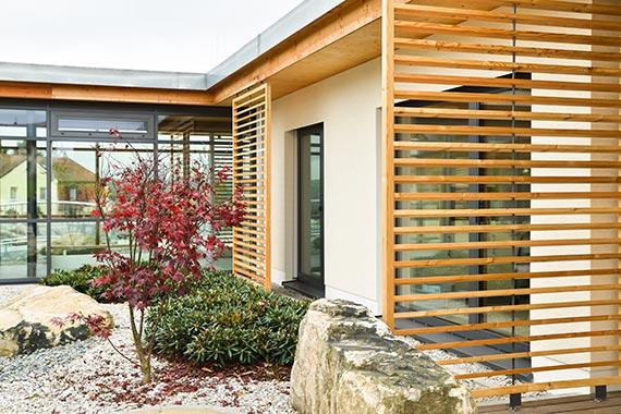 Außenansicht des Seniorenhauses mit Holzelementen und gestaltetem Hof