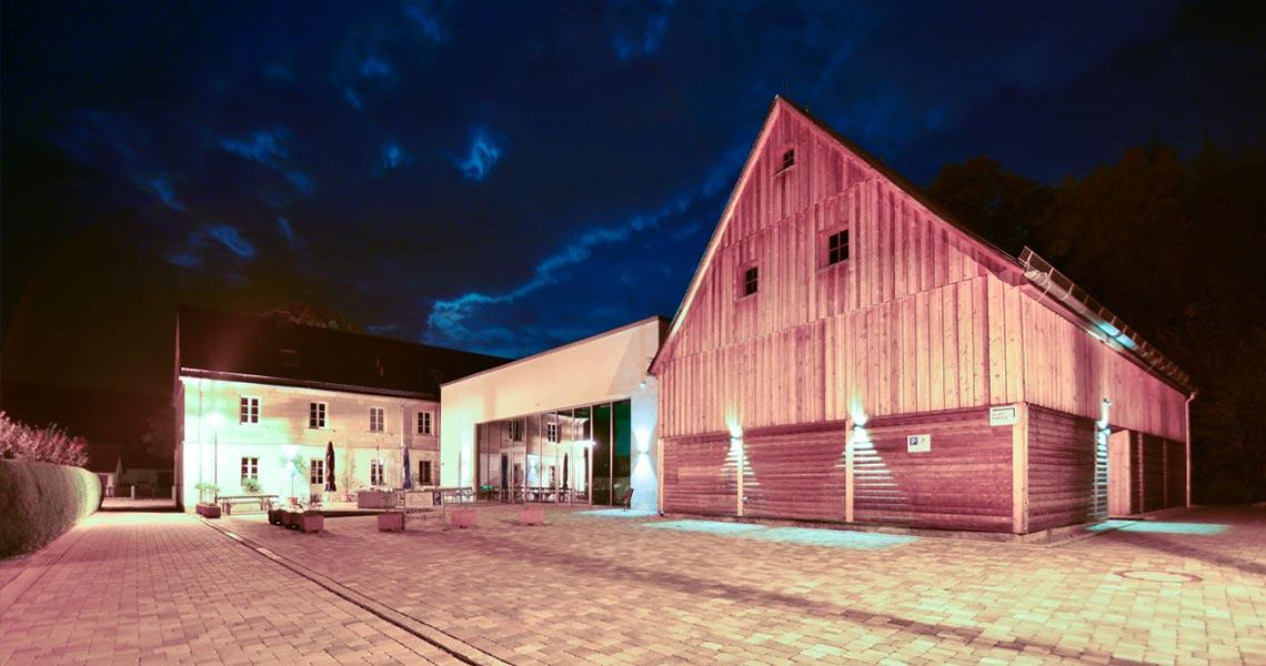 Aussenansicht der Kulturscheune mit gepflastertem Hof bei Nacht