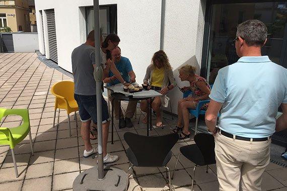 Die Mitarbeiter des Architekturbueros essen Eis auf der Terrasse.