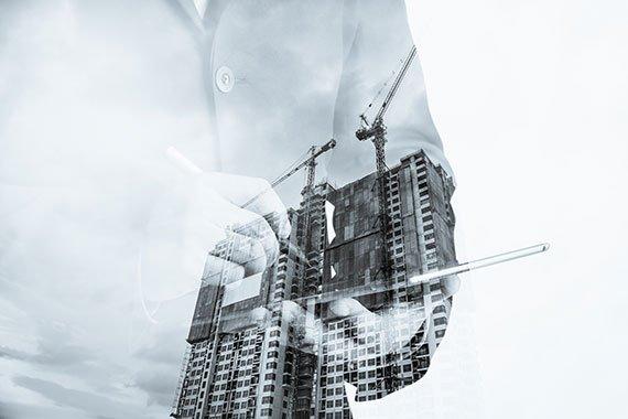 Bild eines Hochhauses mit Kränen und einem Bauleiter
