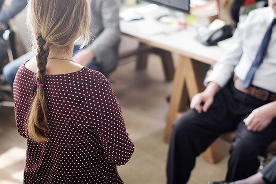 Eine Frau berät Kunden, die im Raum sitzen.