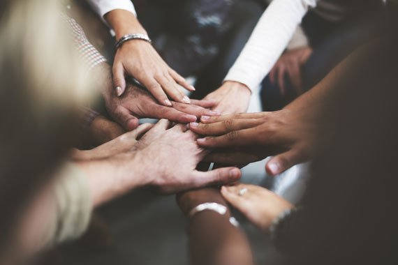 Viele Haende, die Teamzusammenhalt symbolisieren.