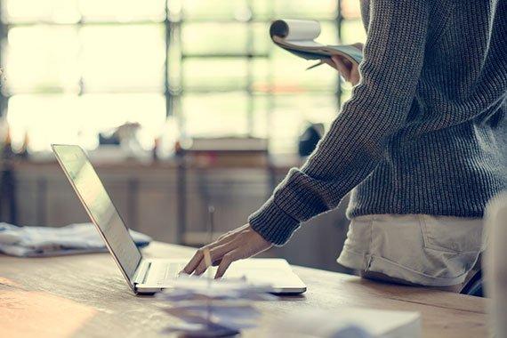 Jemand steht an einem Tisch und bedient ein Macbook.
