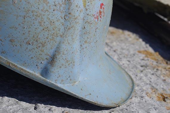 Ein abgenutzter Bauhelm in babyblau mit Dreckspritzern.